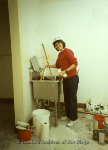 P169.015m.r.t Paradigm Women's Bookstore - Moving in: Karen Merry working by a sink, surrounded by painting supplies