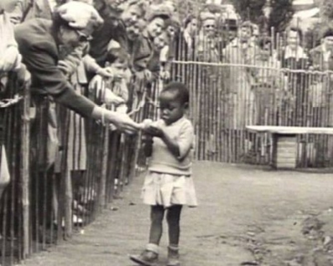 [1958] Human Zoo in Brussels Belgium white spectator interacting with young black child 1958
