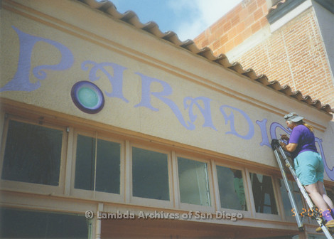 """P167.049m.r.t Paradigm Women's Bookstore: Woman painting """"I"""" in """"Paradigm"""" above store front"""