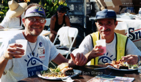 """P119.066m.r.t San Diego Pride 1997: Danny(?) and another man wearing """"Share the Vision"""" t-shirts, sitting with food"""