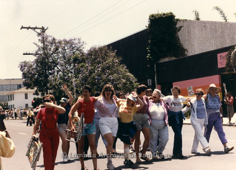 San Diego LGBTQ Pride Parade, July 1988: Members of 'San Diego Lesbian Organization' (SDLO) walking down the street with their arms around each other. Anti-gay fundamentalist christian protesters in the background