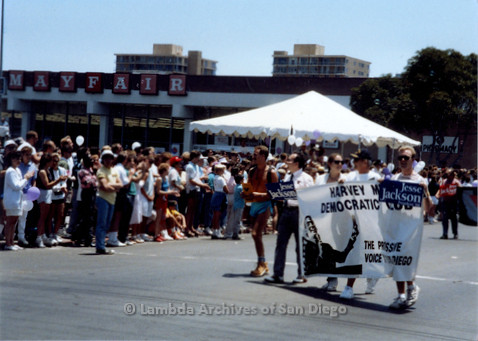 "P018.018m.r.t San Diego Pride Parade 1988: Marchers carrying signs: ""Harvey Milk Democratic Club,"" ""Jesse Jackson President '88"""