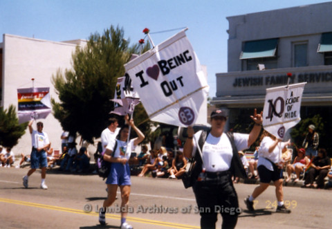 San Diego LGBT Pride Parade 1999: San Diego Pride Parade, July 1999: LGBT Parade Themes Banner Contingent. Wendy Sue Biegeleisen (Front) holds 1983 banner 'I Love Being Out' and Judy Reif on the left,  holds another Theme Banner.