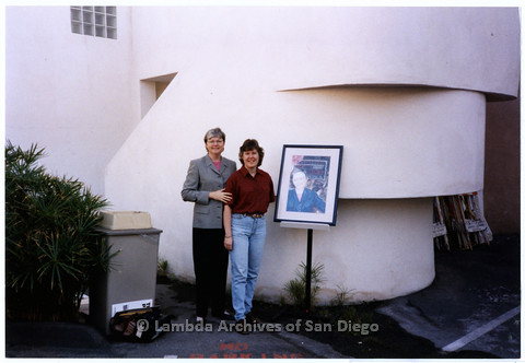 P200.021m.r.t LASD's 10th Anniversary at the Center: Christine Kehoe and her partner, Julie Warren, standing outside by a portrait of Kehoe drawn by Warren