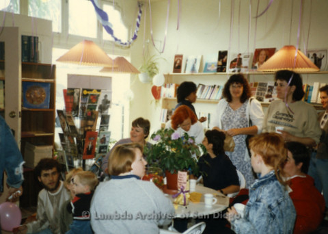 P169.086m.r.t Paradigm Women's Bookstore Grand Opening: People gathered around table in decorated bookstore