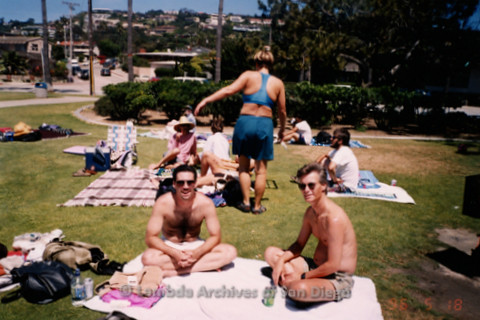 P239.035m.r.t Volunteer Picnic for The Center in La Jolla: Two men sitting on towel, woman in blue bathing suit in background
