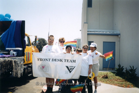 "P234.020m.r.t SD Pride Parade 1996: People holding rainbow flags and banner that reads: ""Front Desk Team"" with The Center and Front Desk Volunteers logos"