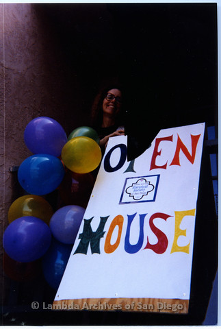 "P200.004m.r.t 1994 Open House: Kate Johnson standing behind ""Open House"" sign"