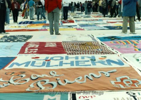 "P019.296m.r.t AIDS Memorial Quilt 1987: Crowd of people observing the AIDS Memorial Quilt, quilt in center reads: ""JOHN MULHERN"""