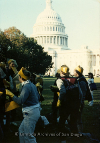 """P019.218m.r.t Second March on Washington 1987: Several men gathered in front of the Capital building, one man with t-shirt that reads: """"Out & Outraged"""""""