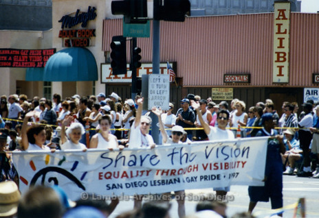 San Diego LGBTQ Pride Parade, July 1997: Judi Schaim (2nd left), Sheila Clark (Center), Judy Reif (3rd  right) and others carry 'Share the Vision: Equality Through Visibility' 1997 theme banner