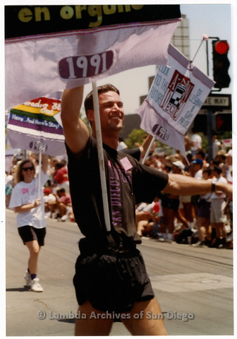P201.008m.r.t San Diego Pride Parade 1992: Glen Dake marching for the Lesbian and Gay Archives, carrying a banner commemorating the 1991 parade; Debbie Zeyher in background carrying a banner for 1988 parade