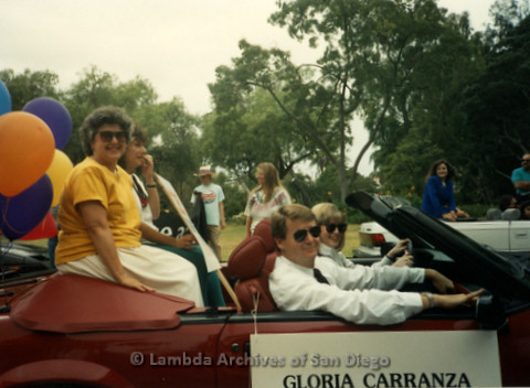 P341.044m.r.t Men and women driving in Pride Parade with a Gloria Carranza sign on car