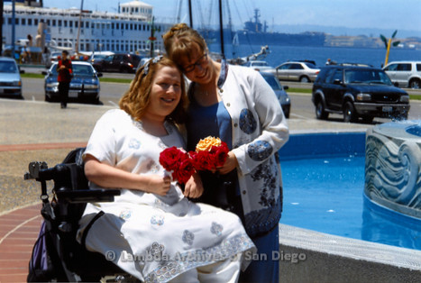P249.004m.r.t First Same Sex Weddings in San Diego: Two women holding flowers outdoors in front of fountain