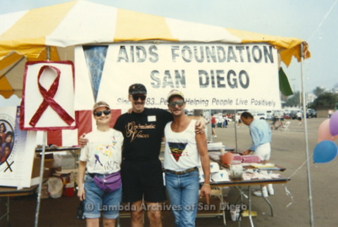 P197.029m.r.t AIDS Walk San Diego 1993: Sharon Parker, Patrick Stevens, and unknown man in front of AIDS Foundation San Diego booth