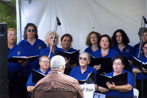 San Diego LGBT Pride Festival, July 2006: San Diego Women's Chorus performing on the LGBT Festival Main Stage with Chris the Conductor (Center Sitting at piano), Carol Reagan-Harlow (far left), Sheila Clark (sitting right, front), Dawn McMarrow (far right