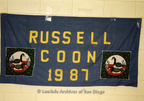 P019.059m.r.t AIDS Quilt at San Diego Golden Hall 1988: Dark blue quilt with patches of ducks dedicated to Russell Coon
