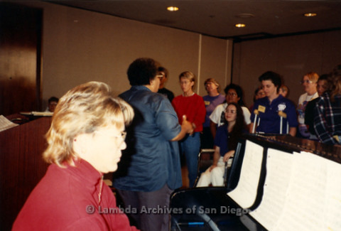 """""""The Magic Music Makes"""" San Diego Women's Chorus (SDWC) first choral festival with Sister Singers 1991: Deborah Morton playing the piano, Cynthia Lawrence Wallace directing, SDWC singing, Sheila Clark (right)"""