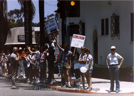 San Diego Lambda Pride Parade: Crowd holding Pro-LGBT signs across the street from Fundamentalist Christian Protesters. Signs read 'Love does not exclude it embraces' and 'Hillcrest welcomes you'.