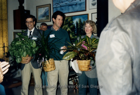 P341.005m.r.t San Diego Democratic Club 1991 installation: Mike Gotch standing between a man and a woman, all holding plants