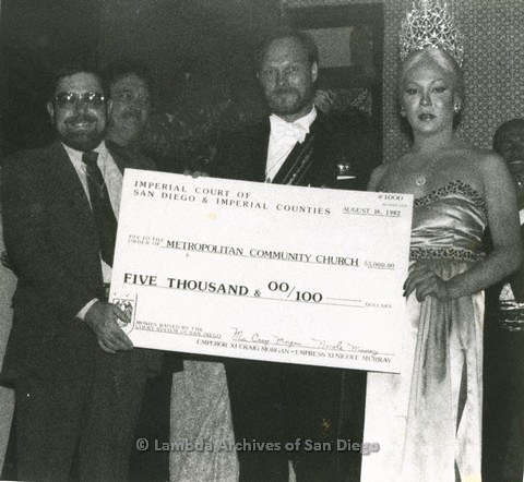 1982 - Empress Nicole Murray-Ramirez (right) and Emperor Craig Morgan (center) of the Imperial Court, Present $5,000 check to Rev. David Farrell (left) benefiting the San Diego Metropolitan Community Church (M.C.C.)