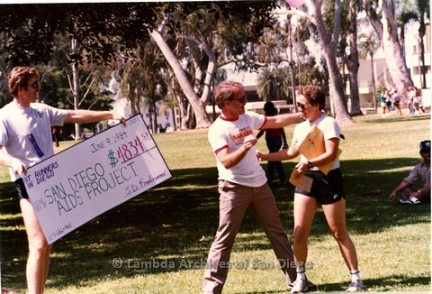 1984 - Jim Ellis (left) of 'Front Runners' presents a check to the San Diego Aids Project during the annual 'Fun Run for Pride'.