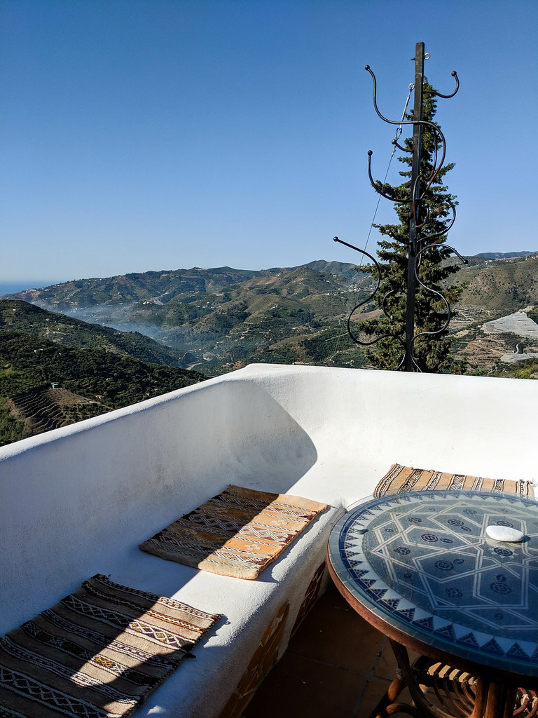 A table and two benches overlooking the valley, with a view of the sea in the right corner