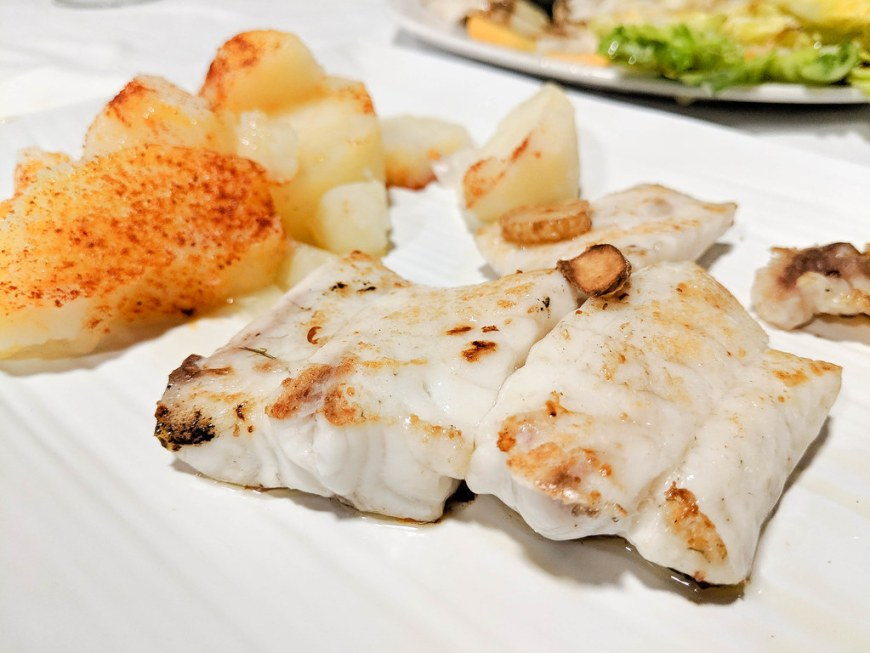 Grilled fish with a side of potatoes dusted with paprika