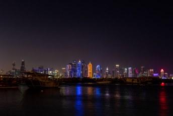 Uitzicht op de skyline van de wijk Al Dafna met de iconische gouden dildo en op de voorgrond een traditionele Qatarese Dhow boot.