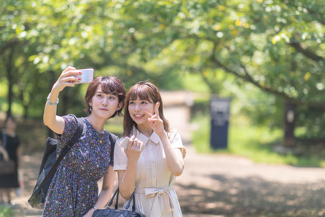 Female students taking selfie pictures in green forest