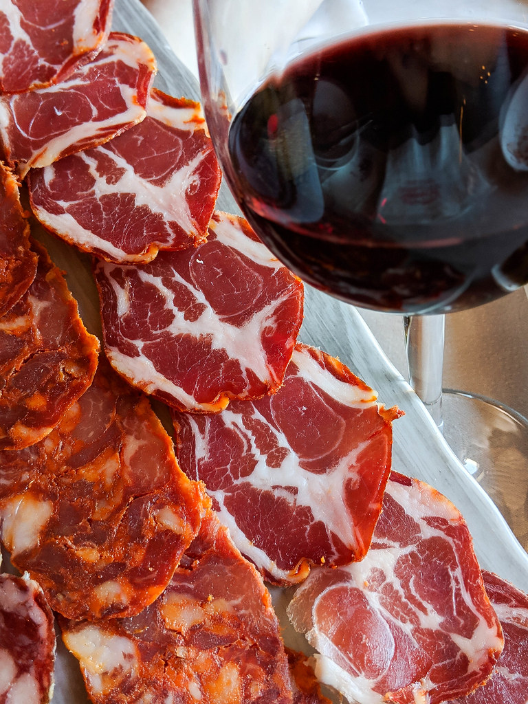 A platter of Iberian salami next to a glass of red wine