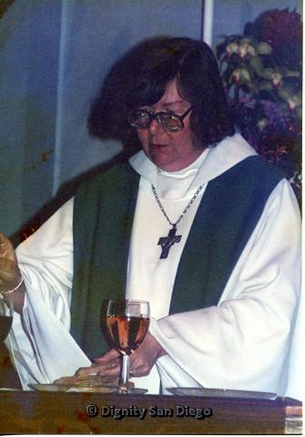P103.033m.r.t Dignity San Diego: Female religious leader handling food item in church