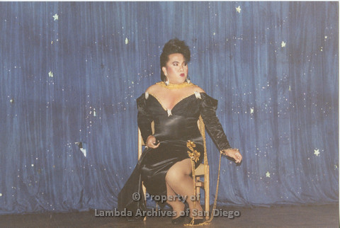 P001.250m.r.t Through The Years Fundraiser: drag queen seated wearing a black dress