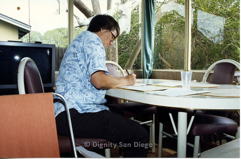 P103.077m.r.t Dignity San Diego: Person in blue writing on top of a table
