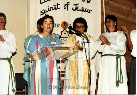 P103.027m.r.t Dignity San Diego: Bridget Wilson speaking at church podium.