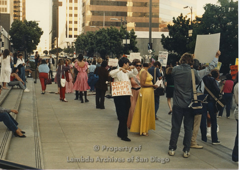 P024.122m.r.t Myth California Protest, San Diego, June 1986: person with a sign around their neck (Coorporate Pimp$ Amerika)