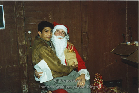 P001.298m.r.t X-mas: man in brown jacket holding a present and sitting on Santa's lap