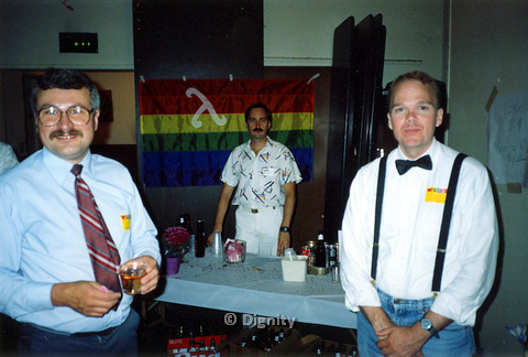 P104.183m.r.t Dignity San Diego: Neil Manfredi (on left) and two other men standing in front of Lambda-bearing rainbow flag.