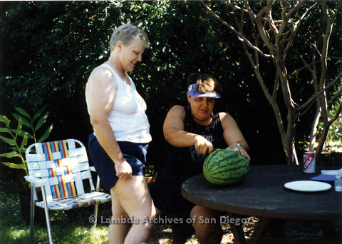 P024.320m.r.t Commonwealth: Sally Hopkins (left) looks on as a woman cuts in to a watermelon.