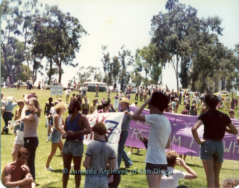 """P109.010m.r.t San Diego Pride Festival 1976: Gathering in Balboa Park. """"200 Years of Freedom"""" banner in background."""