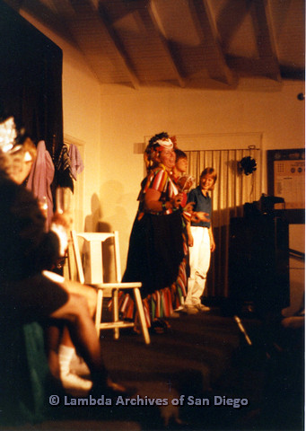 P024.171m.r.t Performers on stage with central figure wearing colorful dress