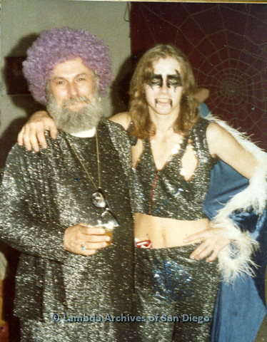 P110.026m.r.t Metropolitan Community Church: Joseph Gilbert wearing purple wig posing with similarly dressed man standing in front of spiderweb backdrop.