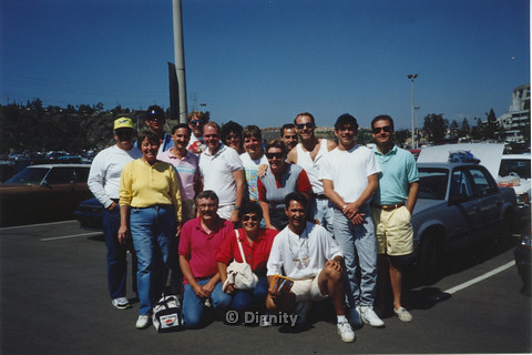 P104.070m.r.t Dignity San Diego: Men and women posing in front of cars at a parkin lot (Bruce Neveu possibly in white tank top)