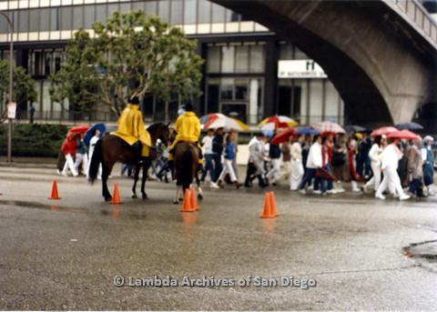 P024.543m.r.t  People with umbrellas walking under a bridge