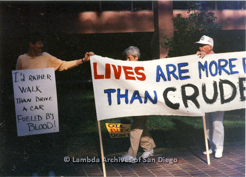 "P024.557m.r.t Judith McConnell  touching sign to the right reading ""LIVES ARE MORE..THAN CRUDE.."""
