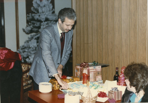 P104.081m.r.t Dignity San Diego: Man in grey suit cutting a cake