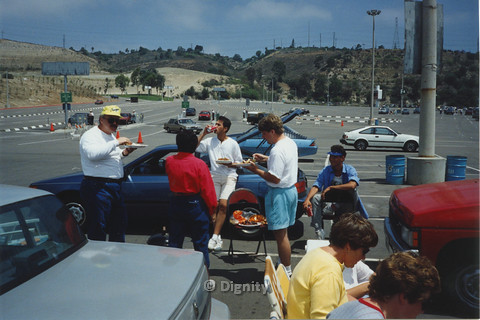 P104.072m.r.t Dignity San Diego: People standing around and eating food at a parking lot