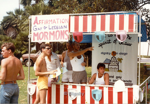 "P104.045m.r.t Diignity San Diego: Bruce Neveu and other men in Dignity San Diego booth, with sign above stating ""AFFIRMATION GAY & LESBIAN MORMONS"""