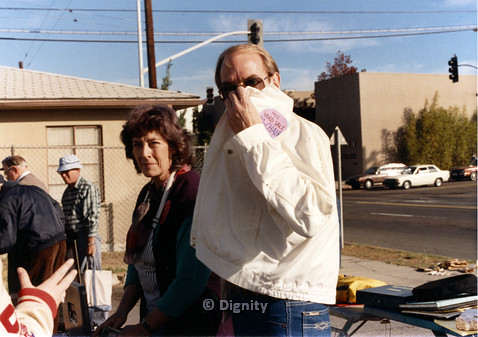 "P104.007m.r.t Dignity church and MCC yard sale: Woman on left, man on right with tag ""MCC yard sale Co-Chair : Ask me… I know everything"" covering half of face"