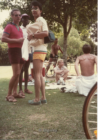 P104.057m.r.t Dignity Picnic 4th of July: Stan (?) standing with two men, with a person and two shirtless men in the background